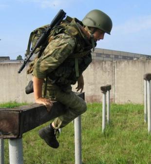 боец в бронешлеме проходит полосу препятствий