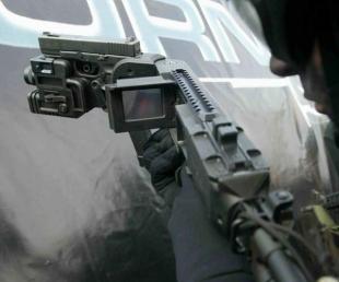 Используется видеокамера, которая собственно заглядывает за угол и цветной LCD монитор. Вот так это выглядит для стрелка